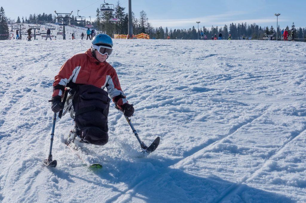 Accessible Travel Adventure Skiing: A skiier uses the Dual Ski adaptive ski to ski down the mountain.