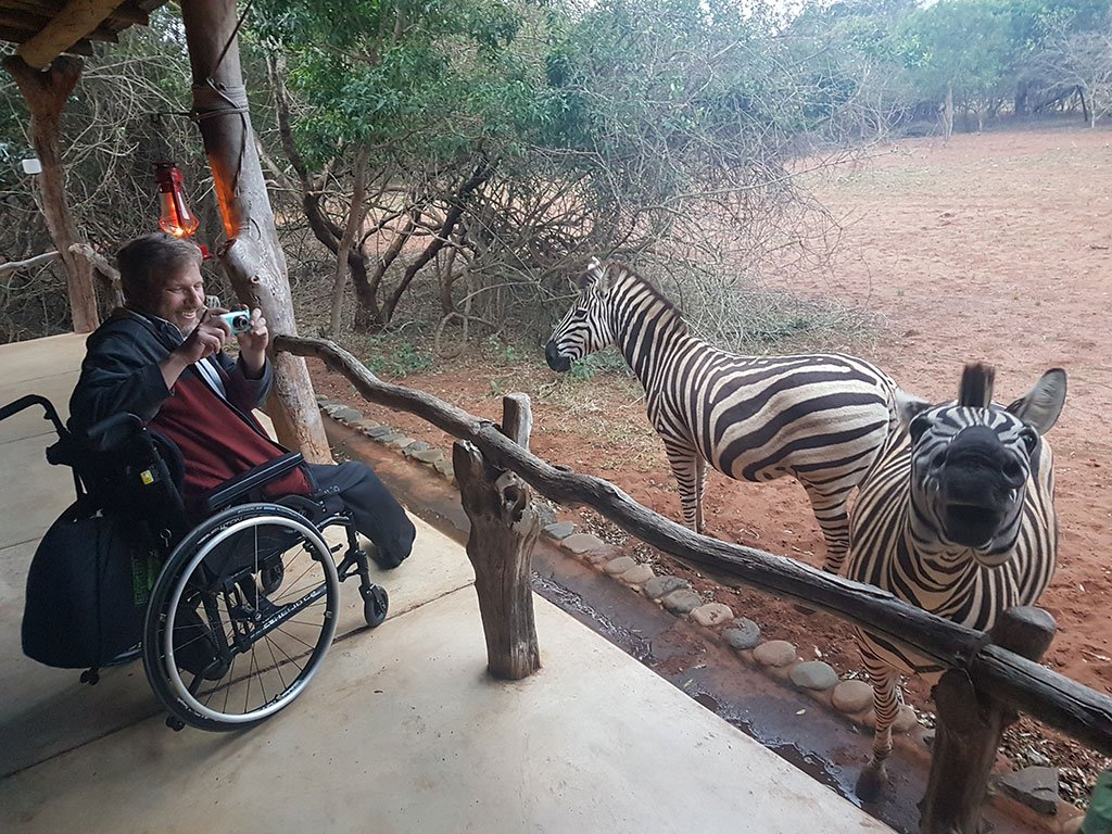 Accessible Travel Adventure Safari: Man in a wheelchair, smiling, takes a picture of two zebra while he is on safari.