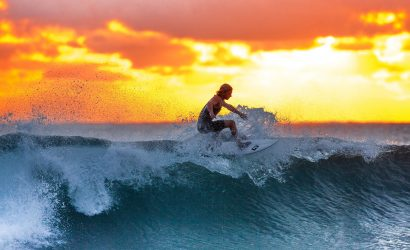 surfer rides a wave in front of a beautiful sunset