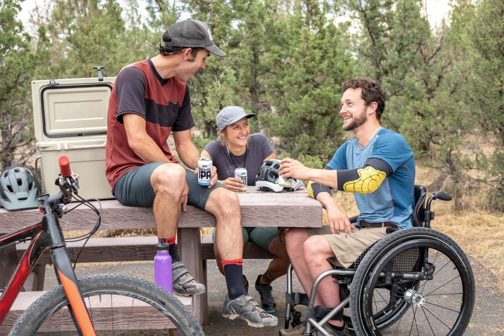 Accessible Travel Adventure Mountain Biking: Friends share a beer after a mountain bike ride, one friend is in a wheelchair.